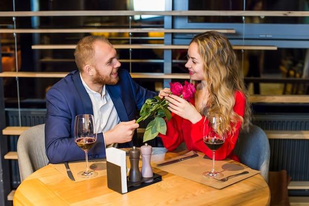 Mann, der der frau rosenblumenstrauß bei tisch gibt Kostenlose Fotos