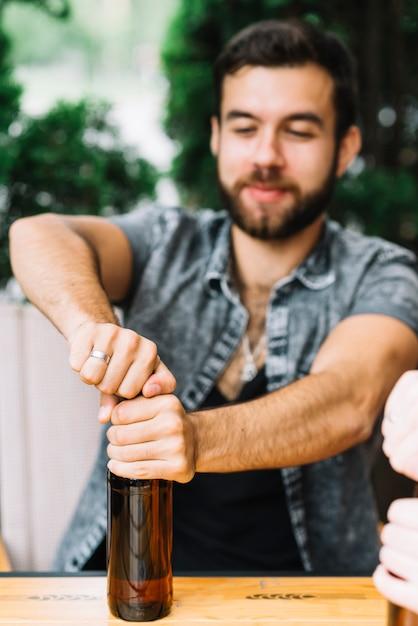 Mann, der die flasche alkohol auf tabelle öffnet Kostenlose Fotos