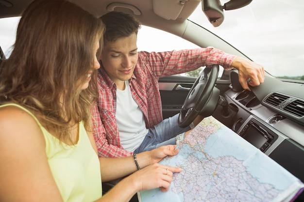 Mann, der die frau zeigt finger auf standortnavigationskarte im auto betrachtet Kostenlose Fotos