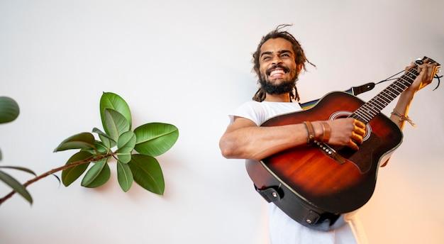 Mann, der die gitarre mit kopienraum spielt Kostenlose Fotos