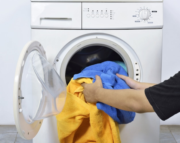 Mann, der die schmutzigen tücher in waschmaschine für gewaschen lädt Premium Fotos