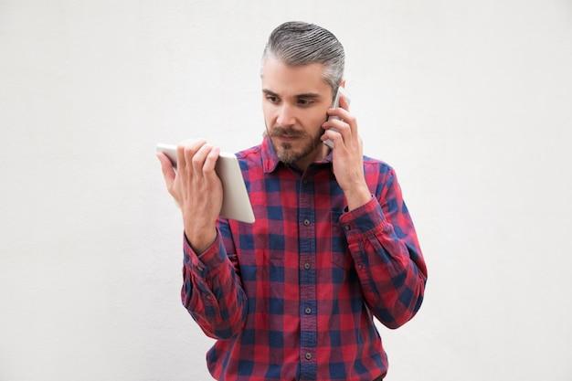 Mann, der digitale tablette verwendet und durch smartphone spricht Kostenlose Fotos