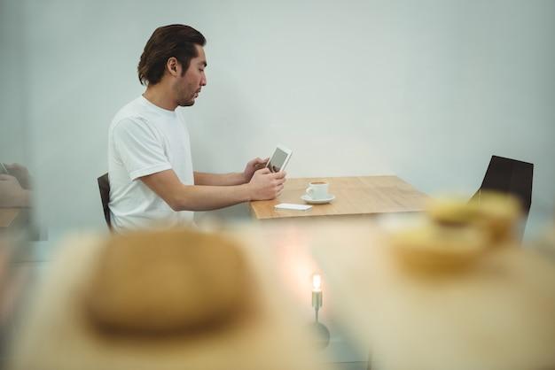 Mann, der digitales tablett im kaffeehaus verwendet Kostenlose Fotos