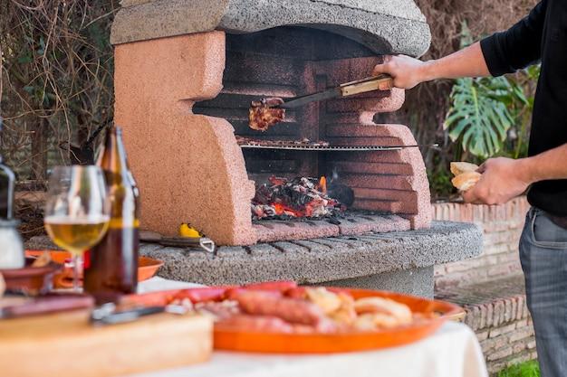 Mann, der draußen fleischsteaks auf grill kocht Kostenlose Fotos