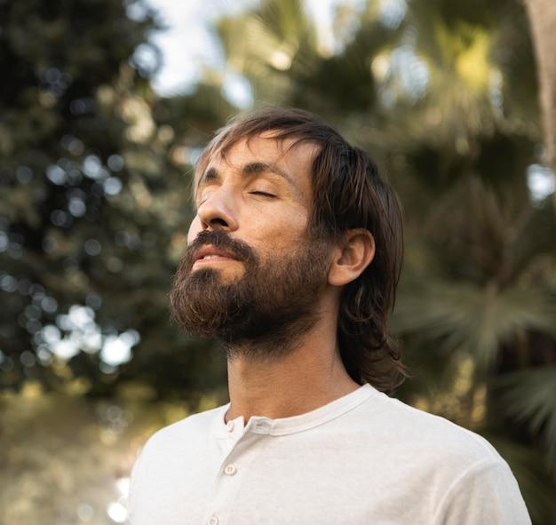 Mann, der draußen meditiert, während er yoga macht Premium Fotos