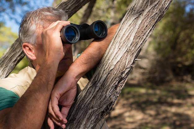 Mann, der durch binokulares durch baum schaut Kostenlose Fotos