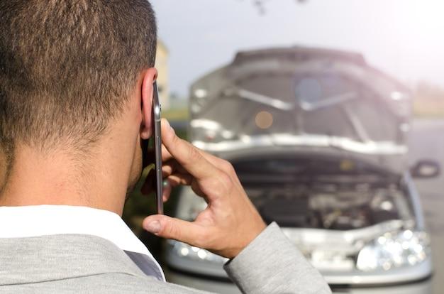 Mann, der durch das kaputte fahrzeug steht, das abschleppdienst ruft Kostenlose Fotos