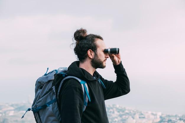 Mann, der durch ferngläser schaut Kostenlose Fotos