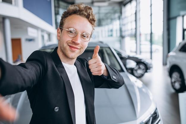 Mann, der ein auto an einem ausstellungsraum kauft Kostenlose Fotos