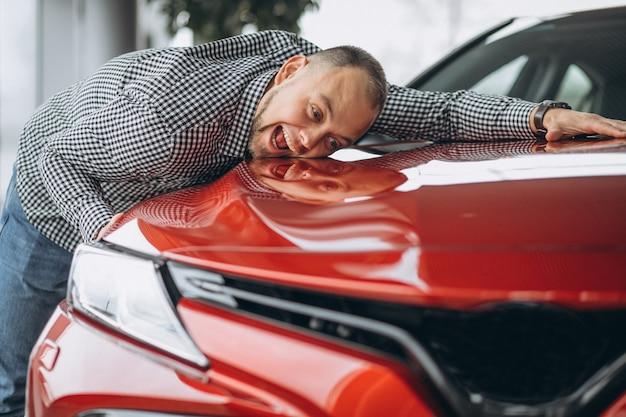 Mann, der ein auto umarmt Kostenlose Fotos