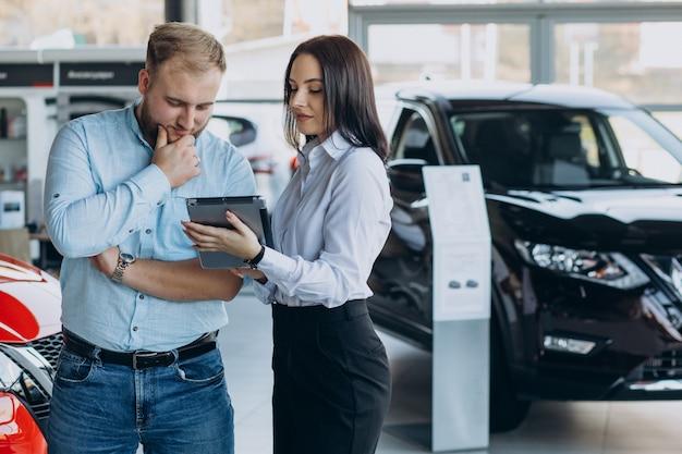 Mann, der ein auto wählt und mit verkäufer spricht Kostenlose Fotos