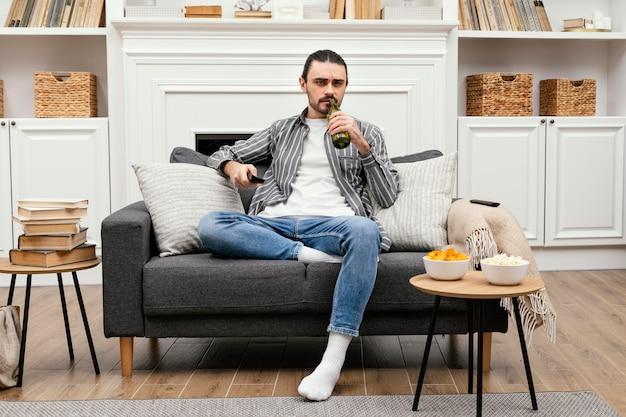 Mann, der ein bier genießt und fernsehen sieht, das auf dem sofa sitzt Kostenlose Fotos