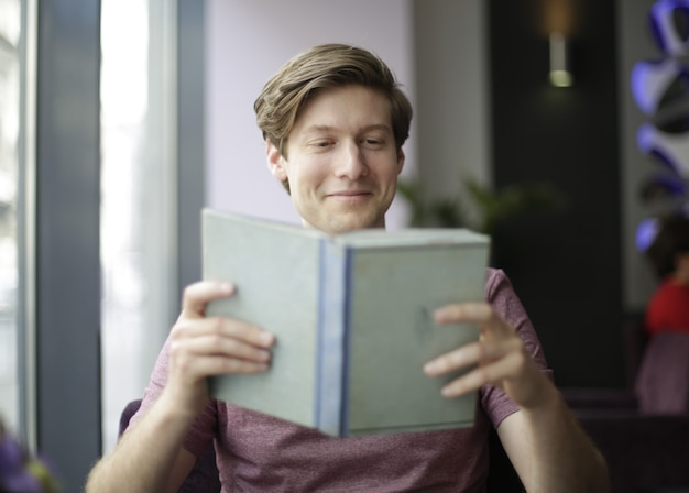 Mann, der ein buch am kaffeehaus liest Kostenlose Fotos