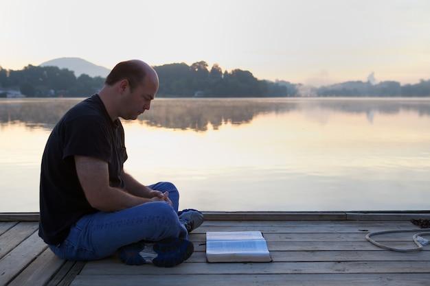 Mann, der ein buch auf einer hölzernen brücke liest, die durch hügel und einen see unter dem sonnenlicht umgeben ist Kostenlose Fotos