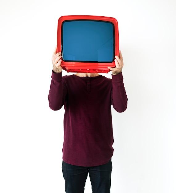 Mann, der ein fernsehen steht und hält Kostenlose Fotos