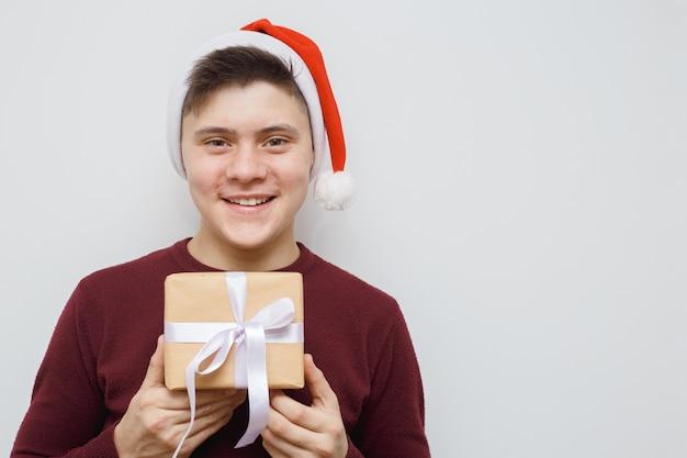Mann, der ein geschenk für jemand anbietet oder zeigt. glücklicher junger hippie mit einem geschenk in den händen. Premium Fotos