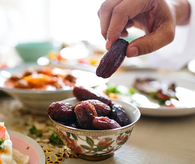 Mann, der ein getrocknetes datum am ramadan-fest hat Premium Fotos