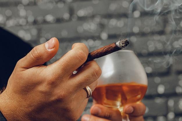 Mann, der ein glas whisky hält und zigarette in den händen nah zündet Premium Fotos