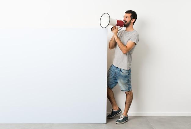 Mann, der ein großes leeres plakat hält und durch ein megaphon schreit Premium Fotos
