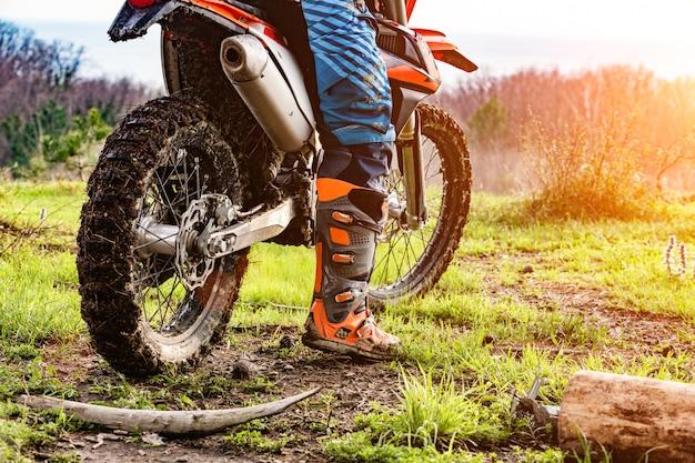 Mann, der ein motocross in einem schutzanzug im schlamm reitet Premium Fotos