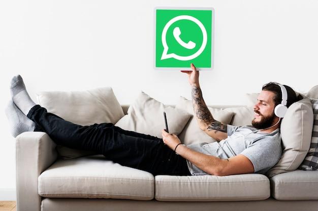 Mann, der ein whatsapp-botenikone zeigt Kostenlose Fotos
