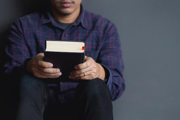 Mann, der eine bibel sitzt und hält. bibel, betend, männer. Premium Fotos