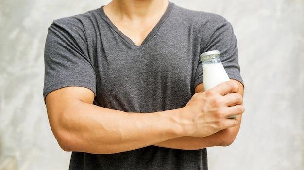 Mann, der eine flasche milch auf grauem hintergrund hält. Premium Fotos