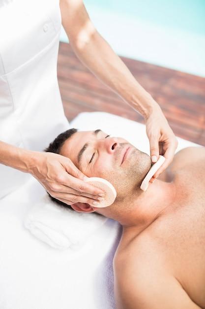 Mann, der eine gesichtsmassage vom masseur im badekurort empfängt Premium Fotos