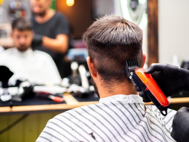 Mann, der eine haarschnitt- und spiegelreflexion erhält Kostenlose Fotos