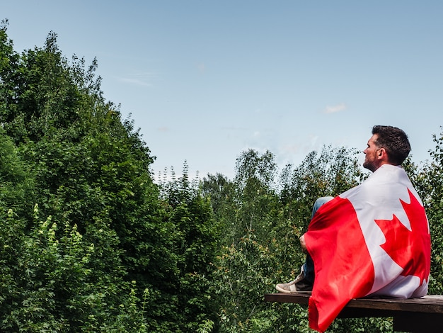 Mann, der eine kanadische flagge hält. nationalfeiertag Premium Fotos