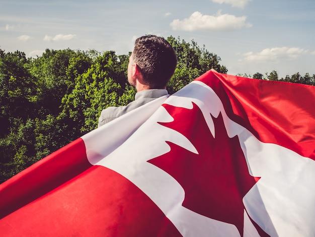 Mann, der eine kanadische flagge wellenartig bewegt. nationalfeiertag Premium Fotos