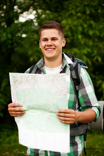 Mann, der eine karte im wald hält Kostenlose Fotos