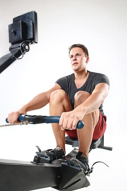 Mann, der eine pressmaschine in einem fitness-club verwendet. Kostenlose Fotos