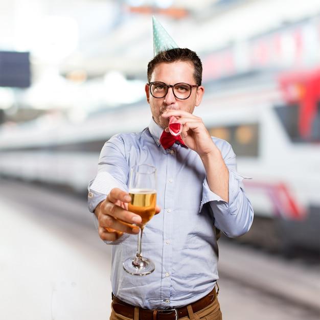 Mann, der eine rote fliege und partei-hut trägt. halten sie einen champagner gla Kostenlose Fotos