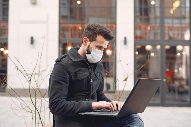 Mann, der eine schutzmaske sitzt, die in der stadt mit einem laptop sitzt Kostenlose Fotos