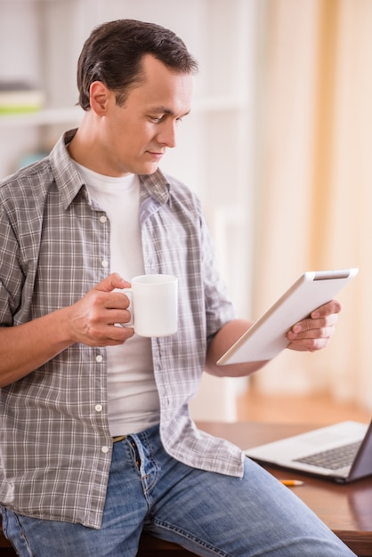 Mann, der eine tasse tee hält und digitale tablette liest. Premium Fotos