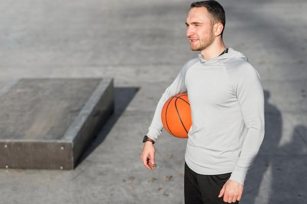 Mann, der einen basketball hält und weg schaut Kostenlose Fotos