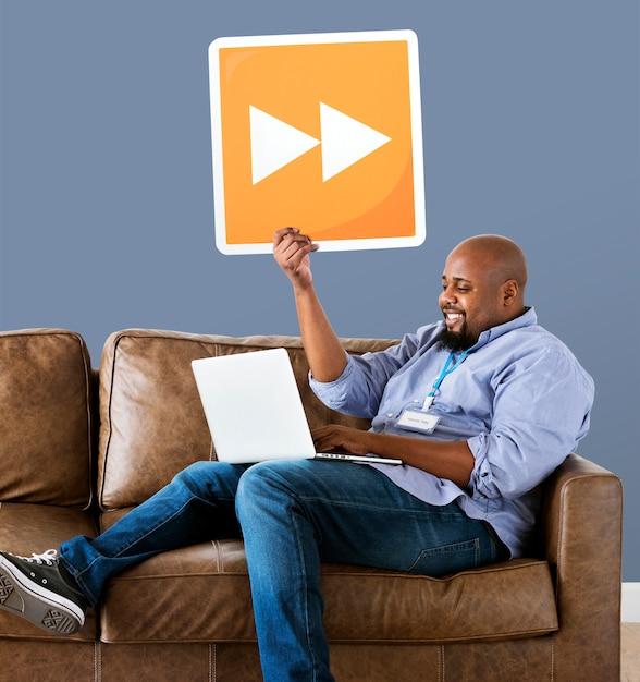 Mann, der einen laptop verwendet und eine taste des schnellen vorlaufs hält Kostenlose Fotos