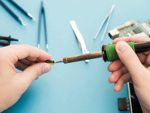 Mann, der einen lötkolben verwendet, um eine komponente zu reparieren Kostenlose Fotos