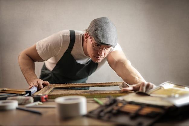 Mann, der einen rahmen repariert Premium Fotos