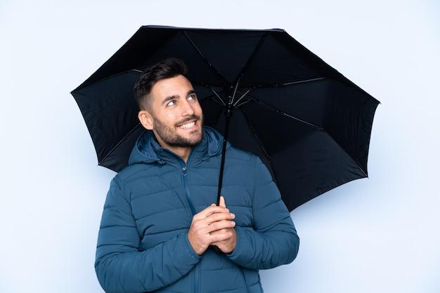 mann der einen regenschirm über isolierter wand mit