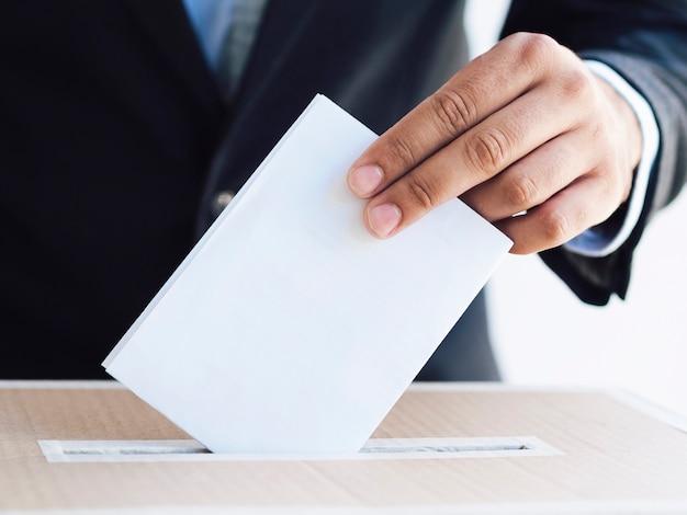 Mann, der einen stimmzettel in eine kastennahaufnahme einsetzt Kostenlose Fotos