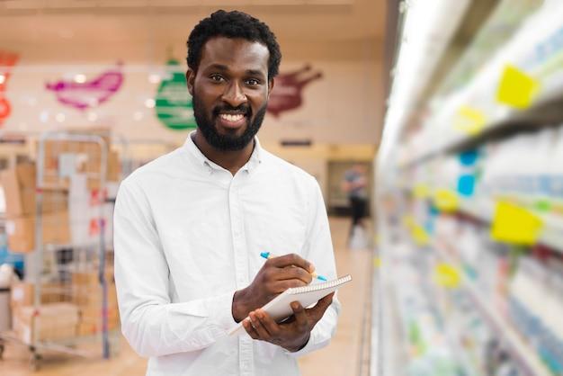 Mann, der einzelteile in der einkaufsliste abhakt Kostenlose Fotos