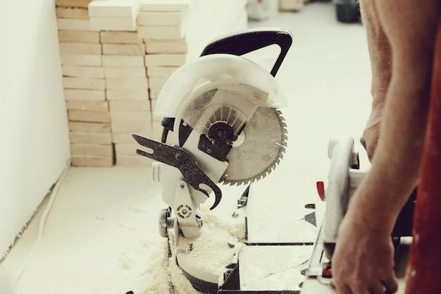 Mann, der elektrische säge an der tischlerei benutzt Kostenlose Fotos