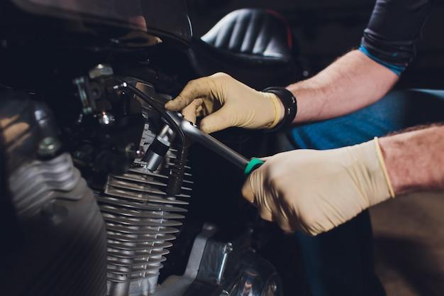 Mann, der fahrrad repariert. zuversichtlich junger mann, der motorrad nahe seiner garage repariert. Premium Fotos