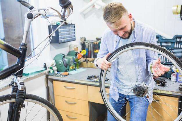 Mann, der fahrradreifen in der werkstatt betrachtet Kostenlose Fotos
