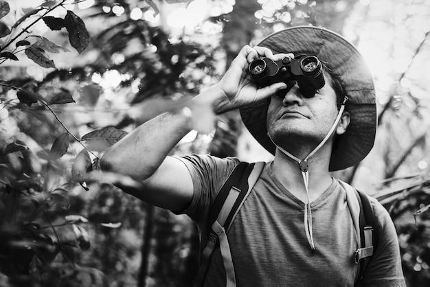 Mann, der ferngläser im wald verwendet Kostenlose Fotos