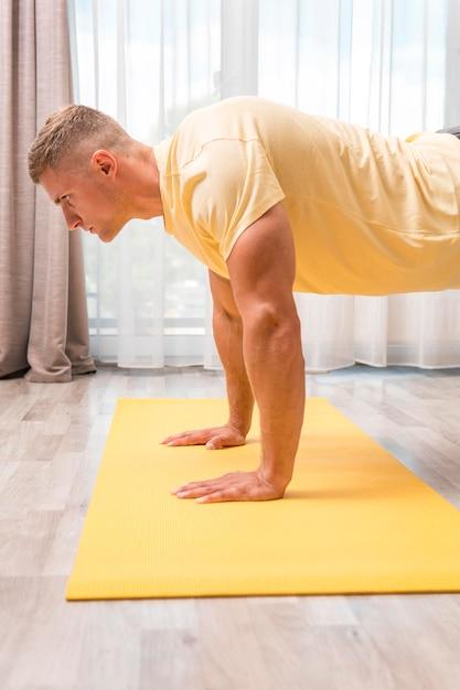 Mann, der fitness zu hause auf matte tut Kostenlose Fotos