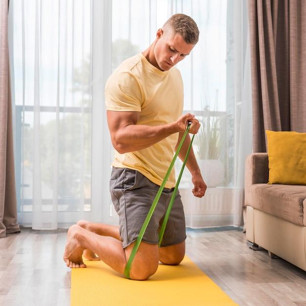 Mann, der fitness zu hause mit gummiband tut Kostenlose Fotos