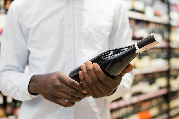 Mann, der flasche wein im alkoholabschnitt kontrolliert Kostenlose Fotos